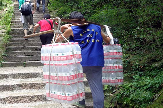 A Chinese porter carries water up China's Huangshan or Yellow Mountain.