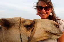 Graduate student Caitie Goddard poses with a camel during her summer internship in Africa.