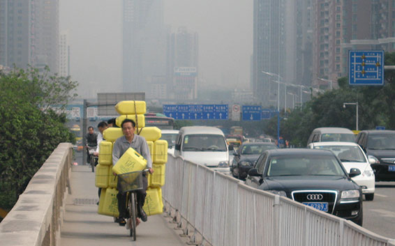 A man hauls waste by bike while a luxury car passes him in the southern Chinese city of Guangzhou. (Credit: William Foreman)
