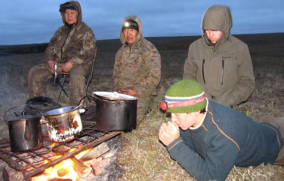 Caleb Fogel gets close to the fire as Chris Whalen watches from behind on the Siberian tundra.
