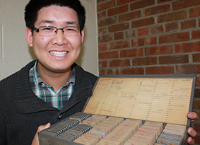 Joseph Ho, a U-M doctoral student in history, holds a box of slides created by U.S. missionaries in China.