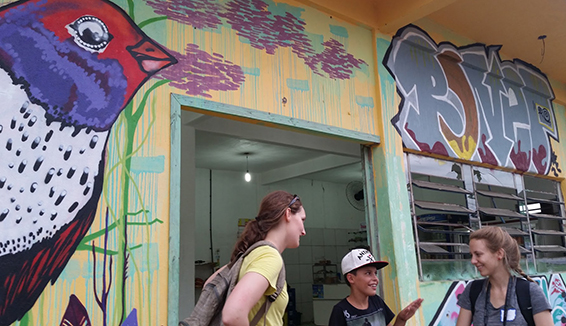 U-M students Charlotte Wilson (left) and Samantha Farr (right) consult with a boy who lives in the Santa Marta community. (Photo courtesy U-M Capstone team.)