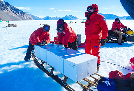 Sarah Aciego, Sarah Aarons and Luca Lanci, a researcher at the University of Urbino in Italy, stand near ice core boxes loaded onto a sled. (Photo by Carli Arendt)
