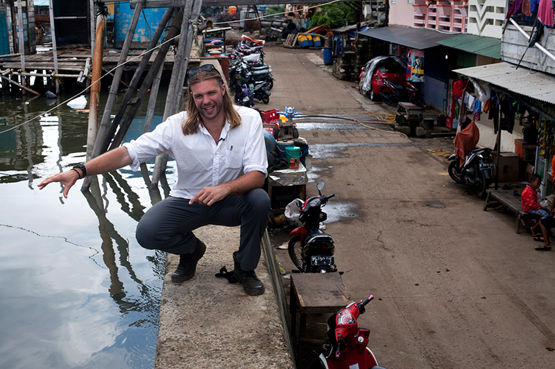 Frank Sedlar sits on the existing sea wall at the Waduk Pluit neighborhood of Jakarta. The barrier is a modest two feet wide concrete wall that is supposed to stop seawater from pouring into urban neighborhoods. According to residents, the water already flows.