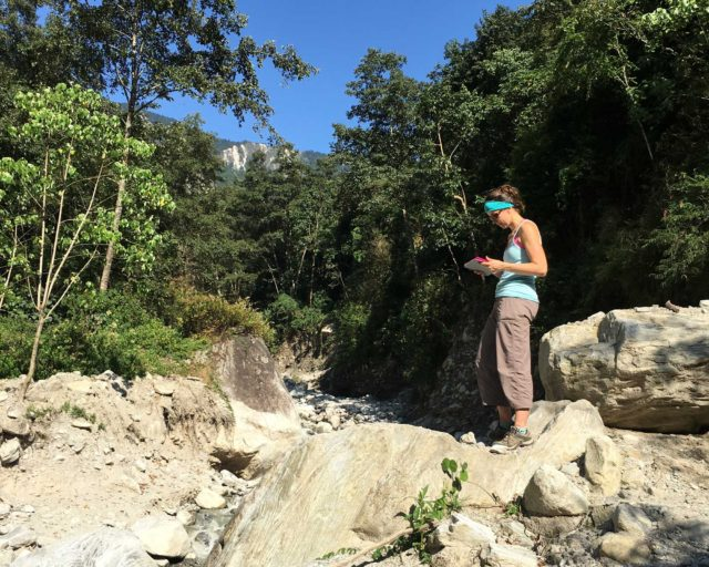 Marin Clark assessing boulders deposited during a monsoon-triggered debris flow near Timbu, Nepal. (Credit: Dimitrios Zekkos)