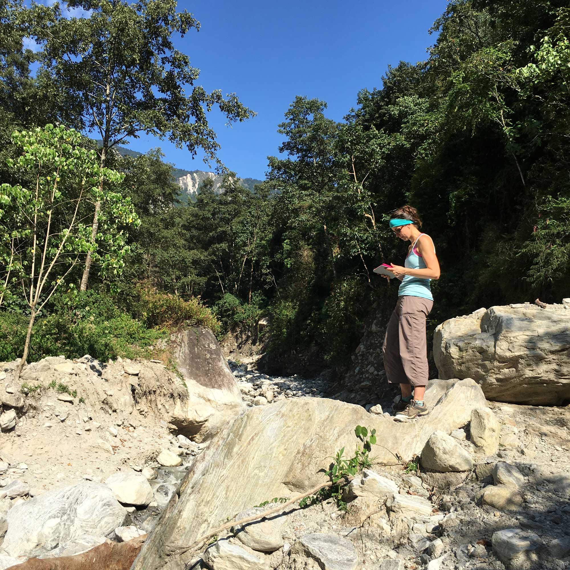 Marin Clark assessing boulders deposited during a monsoon-triggered debris flow near Timbu, Nepal. (Credit: Dimitrios Zekkos)