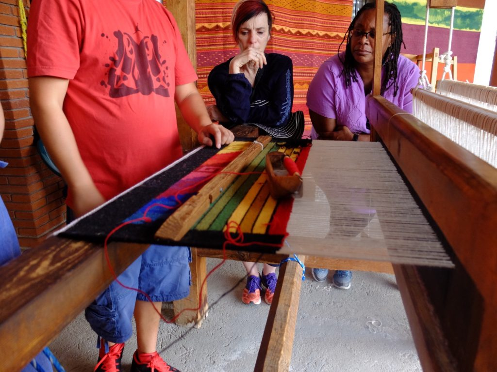 Professors Holly Hughes and Anita González watch a weaving demo in Teotitlan del Valle.
