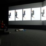 An audience member imitates Mia McKinstry's movements during her video presentation at the Museo del Ferrocarril Projection Room.