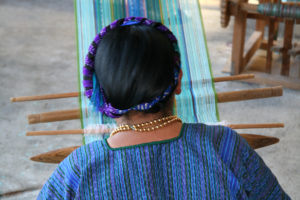 Atitlan, Guatemala - October 31, 2007: Mayan woman weaving on a traditional backstrap loom in village by the lake Atitlan, Guatemala-