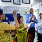 SPH Dean Martin Philbert and faculty Mousumi Banerjee talk to FCAB members ad they visit a clinic and nutrition center in Bagdumur.