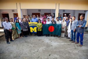 School of Public Health delegates, FCAB members, kids and villagers of Bagdumur come together to hold University of Michigan and Bangladesh flags.