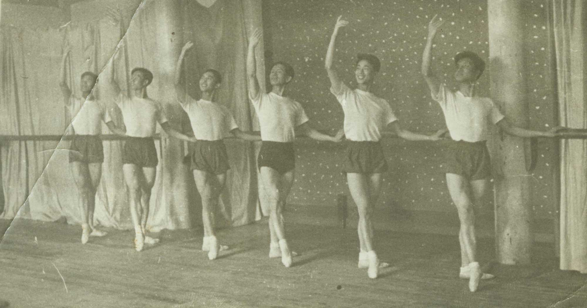Male dancers pose at the ballet bar. Contributor: Zhao Dexian 赵得贤/조 득현 (1913-2002)