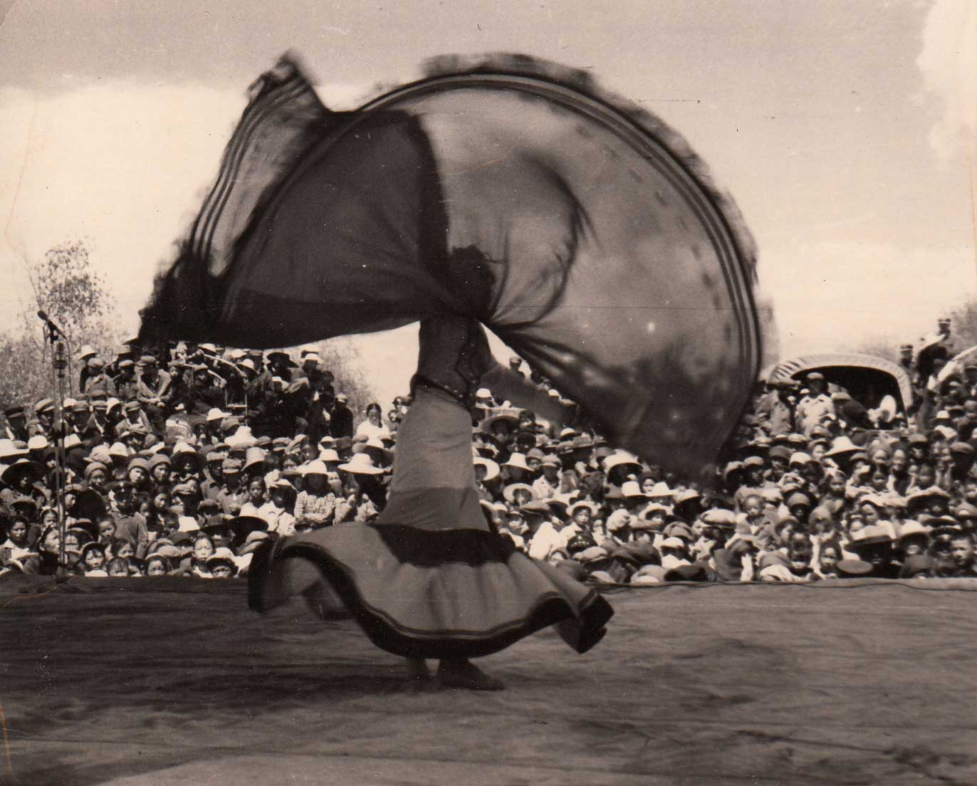 "Bai-Chinese dancer Dong Lixin performs the Yi-style dance solo ""Red Shawl"" 红披毡 on an open-air stage. Contributor: Dong Lixin 董丽馨 (b. 1946)"