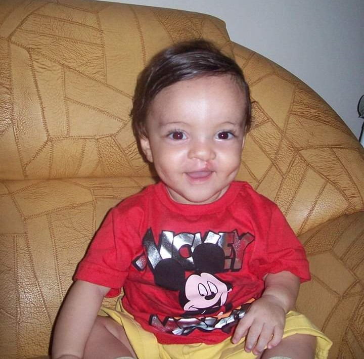 Arthur photoed sitting up on a couch wearing a Mickey Mouse shirt smiling.