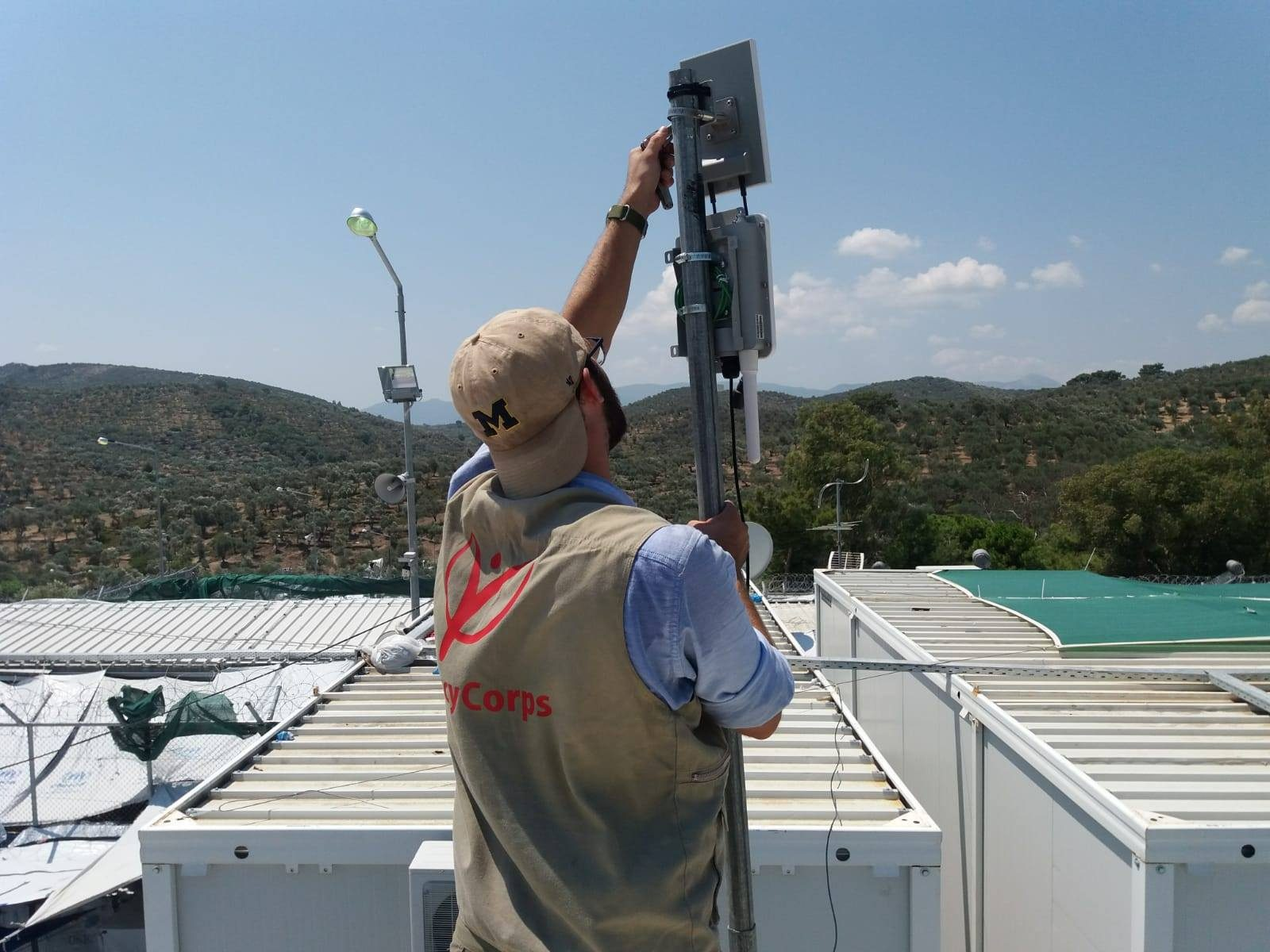 John Traylor bolts down new wireless access points for portions of camp Moria, Greece (photo by Robert Claro).