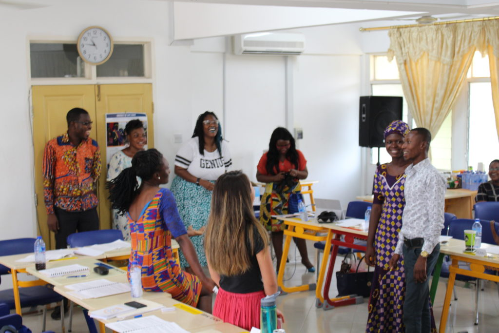 University of Michigan student Briana Sanders answers questions and laughs with students from the University of Cape Coast about her sexual health jeopardy game. Image courtesy: U-M School of Nursing