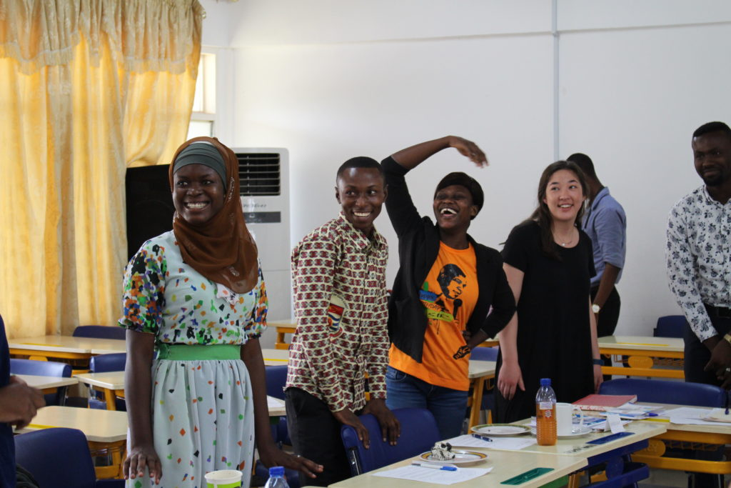 University of Cape Coast students and University of Michigan student, Caitlin Choi, laugh as they engage in an interactive exercise to learn about facilitator training. Image courtesy: U-M School of Nursing