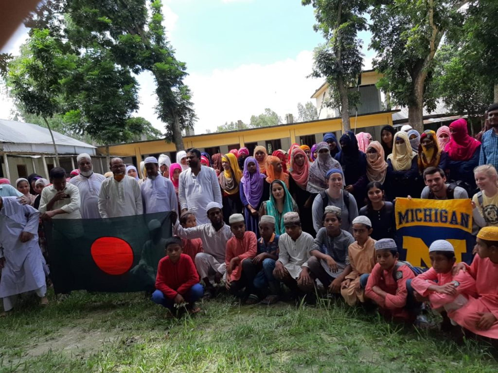 U-M students from M-Heal pose with members of the local Bangladeshi community.