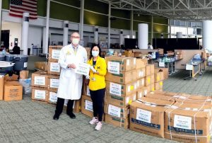 U-M Professors Joseph Kolars and Amy Huang receiving medical supplies from Michigan Medicine's partners in China. The shipment contained thousands of items, including masks, coveralls, and goggles, to fortify the university's virus relief efforts.