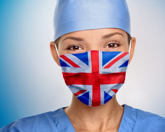 UK flag on british doctor woman wearing medical mask on blue background. United Kingdom flag print graphic design banner. Image credit: iStock