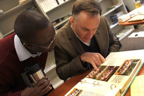 Brian Arbic and Joseph Ansong flip through Arbic's Ghana scrapbook