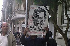 An Egyptian protester holds up a sign of former President Hosni Mubarak as a monster. Credit: Mona from Wikimedia Commons.