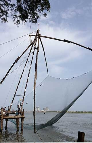A man fishes with a Chinese net in Kochi, India.