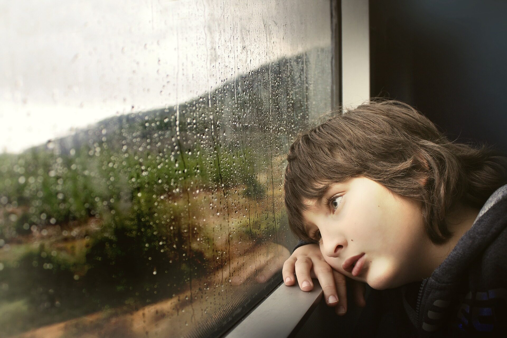 A young boy looks out a window. Image credit: Pixabay.com
